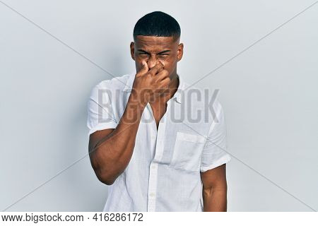 Young black man wearing casual white shirt smelling something stinky and disgusting, intolerable smell, holding breath with fingers on nose. bad smell
