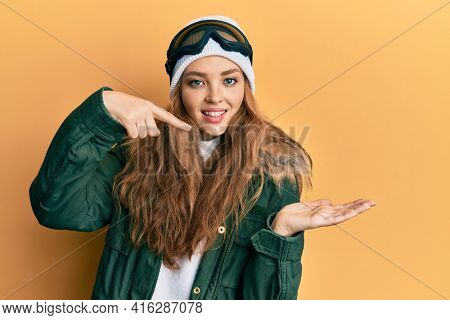 Beautiful blonde caucasian woman wearing snow wear and sky glasses amazed and smiling to the camera while presenting with hand and pointing with finger.