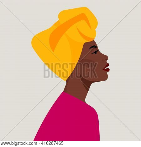 Portrait Of Black Woman In A High African Turban. Wrapped Yellow Turban On The Head. Female Portrait