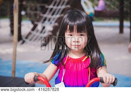 Closeup Cute Asian Girl Riding Red Bicycle. Child Play In Playground. Warm Sunshine. Sweet Smile Kid
