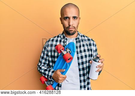 Hispanic adult skater man holding skate and graffiti spray depressed and worry for distress, crying angry and afraid. sad expression.