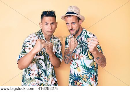 Young gay couple of two men wearing summer hat and hawaiian shirt ready to fight with fist defense gesture, angry and upset face, afraid of problem