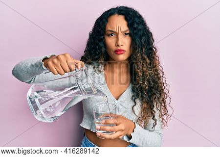 Young latin woman pouring water skeptic and nervous, frowning upset because of problem. negative person.