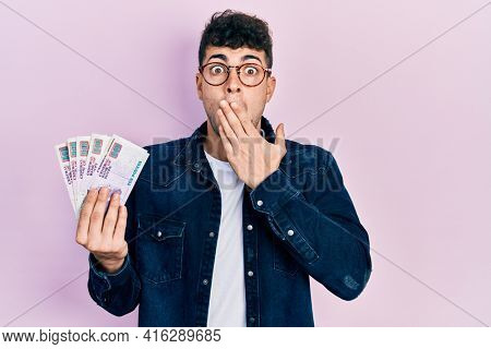 Young hispanic man holding egyptian pounds banknotes covering mouth with hand, shocked and afraid for mistake. surprised expression