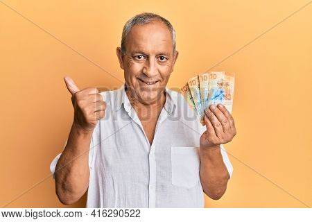 Handsome mature man holding swiss franc banknotes smiling happy and positive, thumb up doing excellent and approval sign