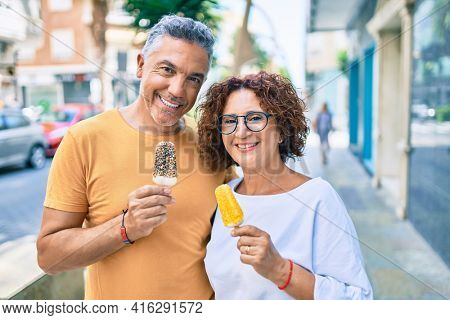 Middle age couple smiling happy eating ice cream at street of city.