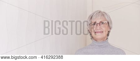 A Portrait Of A Smiling Wearing Glasses Elderly Caucasian Woman With Short Gray Hair On A Light Back