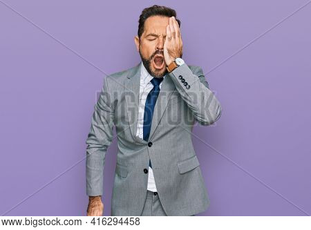 Middle age man wearing business clothes yawning tired covering half face, eye and mouth with hand. face hurts in pain.