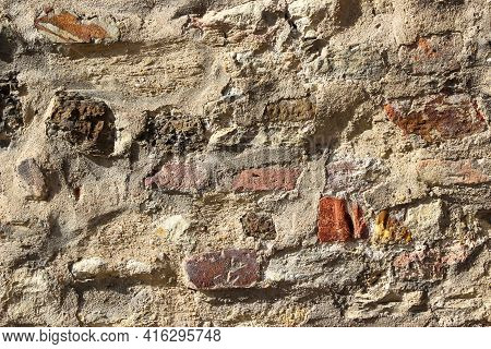 Texture Of An Old Damaged Brick Wall Coated With Heavily Damaged Plaster As A Background