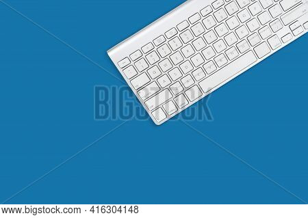 White Computer Keyboard On Sky Blue Background With Copy Space