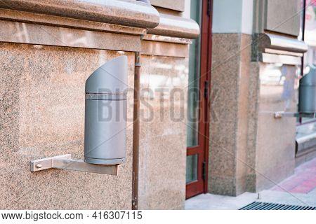 Outdoor Exterior Cylinder Lamp On Granite Wall. External Illumination Installed On Facade To Light B