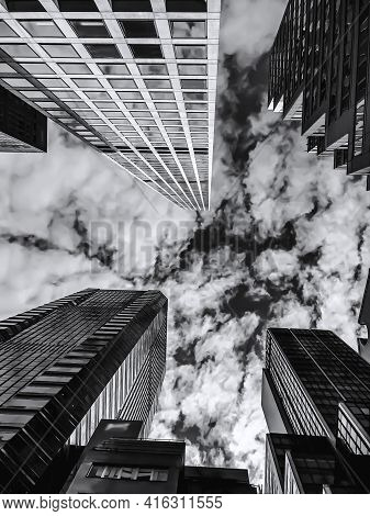 Partly Cloudy Sky Over Skyscrapers In Nyc, From An Upward Perspective. The Focus Is On The Cloudy Sk