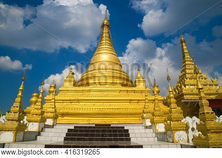 One Of The Golden Stupas Of The Buddhist Temple Kuthodaw Pagoda Against The Background Of The Cloudy