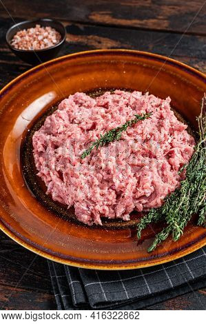 Ground Chicken Or Turkey Meat, Raw Poultry On Rustic Plate With Herbs. Dark Background. Top View
