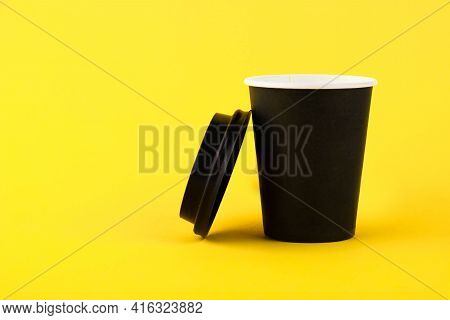 Eco Black Paper Cup, Coffee Paper Cup On Yellow Background. Mockup For Your Advertisement. Copy Spac