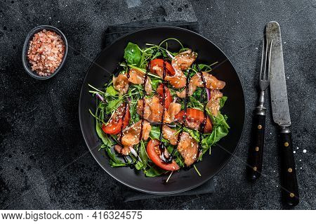 Salmon Salad With Fish Slices, Arugula, Tomato And Green Vegetables. Black Background. Top View