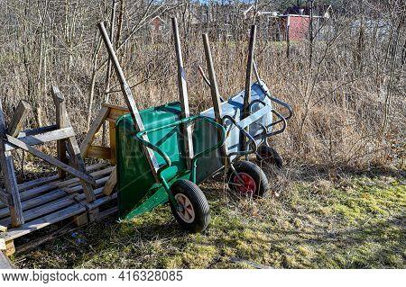Three Wheelbarrows Standing In A Back Garden