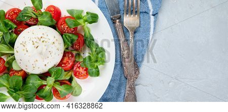Delicious Salad With Sliced Tomatoes And Burrata On Light Gray Background.