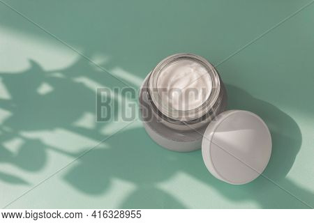 White Cream In Glass Jar On Soft Blue Background. Hard Leaf Shadows On Concept Of Skincare Cosmetic.