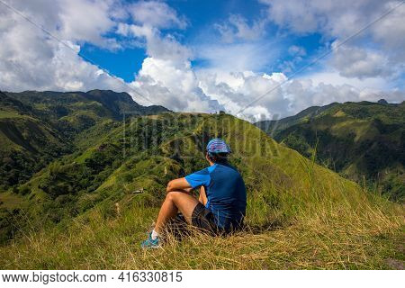 Trekker On The Top Of Hill On Natural Mountain Landscape. Tourist Travels Through The Mountains. Pho