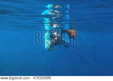 Woman With Photo Camera Undersea In Fish Colony. Open Water Of Deep Blue Ocean. Snorkeling In Open S