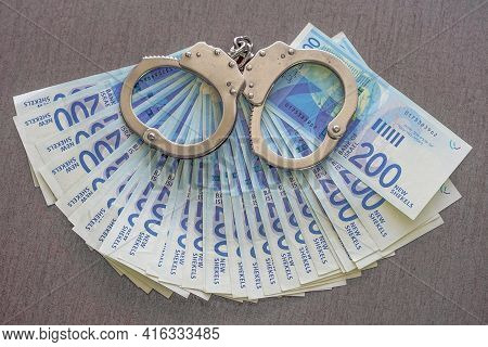 Handcuffs On The Background Of Israeli Money. Police Handcuffs. Financial Crime, Dirty Money And Cor