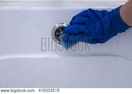 A Blue-gloved Hand Wipes The Dirty Bathroom Drain With A Sponge Filled With Cleaning Agent. Househol