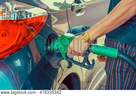 Close-up Hand Using Petrol Pump. Man Hand Holding A Fuel Pump At A Station