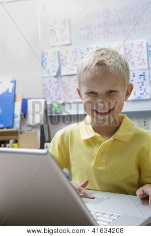 Portrait of a happy preadolescent boy using laptop against whiteboard in classroom