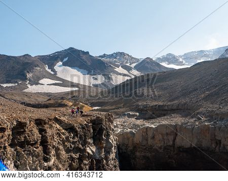View Of The Opasny Canyon Near The Mutnovsky Volcano. Tourists Stand Near The Edge Of The Canyon And