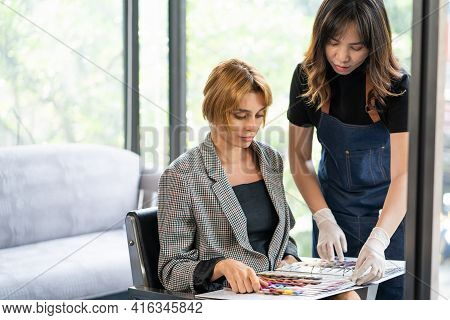 Young Pretty Caucasian Women Sitting Inside Hair Salon, Smiling While Choose New Hair Dye Color And