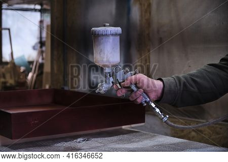 Close-up Man Using Protective Gloves Painting Wooden Timber With Spray Paint Gun. Spray Gun Getting