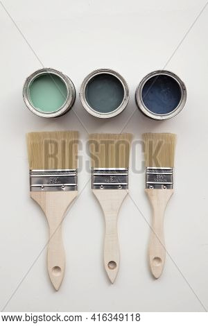 Overhead View Of A Diy Paint Brush With Green And Blue Sample Paint Pots