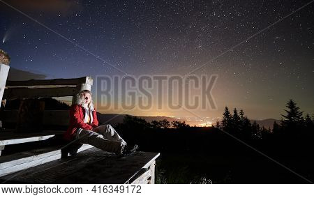 Female Traveler In Red Jacket Sitting On Wooden Steps Under Majestic Colorful Sky With Stars. Magnif