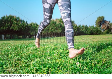 Sporty Barefoot Woman Running On The Green Grass. Young Female Legs Running Barefoot