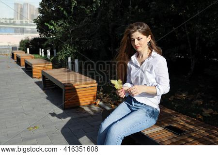 Young Beautiful Pensive Woman Sits On Bench In Deserted Place Outdoors In Sunny Summer Day