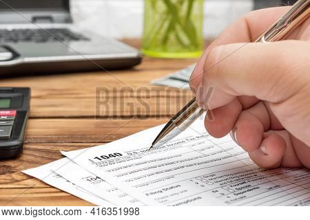 Man Filling Tax Form At Workplace. Close Up.