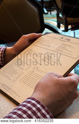 Chicago, Illinois, United States - Dec 11th, 2015: Close Up Of Man Finger With Menu Choosing Dishes