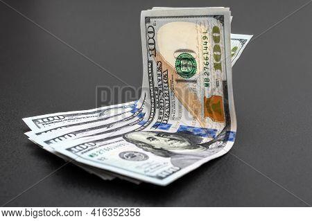 One Hundred Dollar Bills On A Black Background.