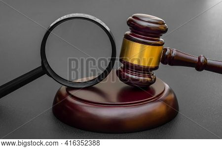 Judge's Gavel With Magnifying Glass On Black.