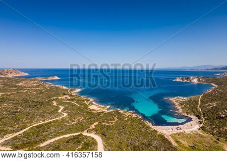 A Boat Sits In A Bay On The Turquoise Mediterranean Sea At Plage De L'alga At La Revellata Near Calv