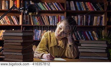 Tired Girl Writes Home Assignment On Sheet Of Paper With Pencil And Yawns Sitting Among Book Stacks