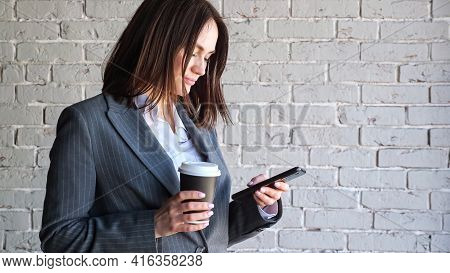 Smiling Businesswoman With Short Dark Hair Types On Black Smartphone Holding Paper Coffee Cup Standi