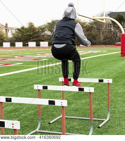 A High School Boy At Track Practice Is Jumping Over A Row Of Hurdles Set Up For Strength And Agility