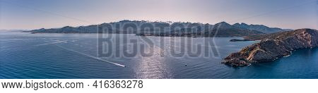 Panoramic Aerial View Of Boat Passing Revellata Lighthouse On A Rocky Promontory With The Citadel Of