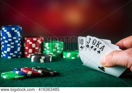 Poker Cards With Royal Flush Combination. Close Up Of Gambler Hand Takes Playing Cards In Poker Club