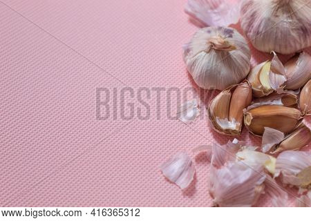 The Photo Shows Purple Garlic. Garlic Lies On A Pink Background. Two Heads Of Garlic Whole And With