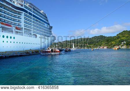 COXEN HOLE, ROATAN, HONDURAS - DEC 26 2012: The Cruise Ship MSC Poesia lays at anchor at the port of Coxen Hole, Roatan, Honduras.
