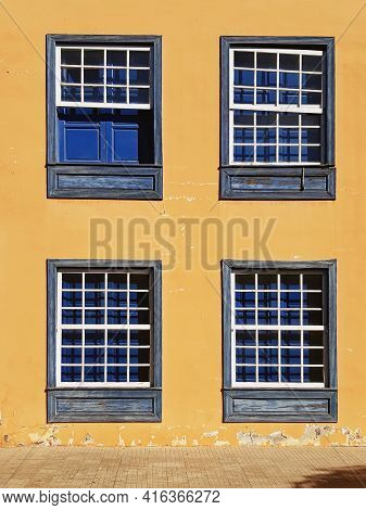 Fragment Of The Old Facade With Closed Vintage Windows. Traditional Guillotine Windows Front View. F