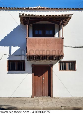 Typical Canarian Facade With Balcony, Door And Wooden Windows On A White Facade. Typical Balcony Of